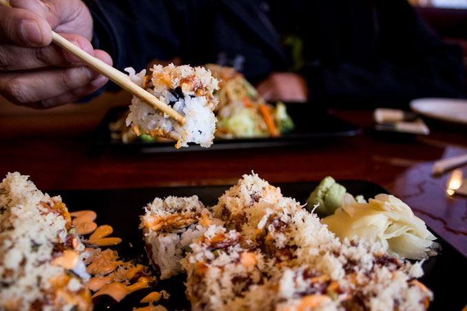 Hand using chopsticks to pick up sushi from plate at Ocean Sushi and Teriyaki